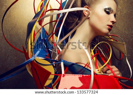 Arty portrait of a fashionable young woman with a perfect golden make-up in a cape done in avant-garde (a-la constructivism and suprematism) and vintage style. Close up. Studio shot
