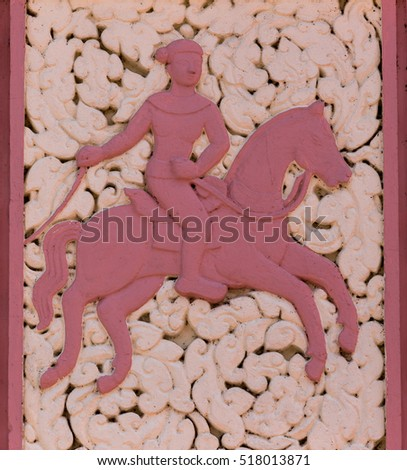 arty portrait of  impetuous soldier riding a large running  horse painting in lateral view from left to right side on a sacred wall a Thai buddhist temple in Nakhon Panom , Thailand. Nobody in frame. #518013871