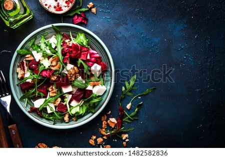 Arugula, Beet and cheese salad with fresh radicchio and walnuts on plate with fork, dressing and spices on blue kitchen table background, place for text, top view Stock photo ©