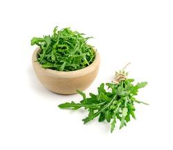 Arugula bunch, ruccola in wood bowl isolated. Fresh arugula leaves, rucola, eruca or garden roquette