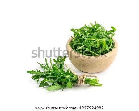Arugula bunch, ruccola in wood bowl isolated. Fresh arugula leaves, rucola, eruca or garden roquette ストックフォト ©