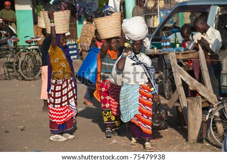 ARUSHA, TANZANIA - AUGUST 11: Unidentified woman at a crowded local market near Arusha, Tanzania, on august 11, 2010. Woman usually carry their merchandise in big baskets on their heads