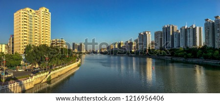 As a merged panorama, this photo provided a wide-angle view of urban landscape of the Xi'zhi River in Huizhou, China at the golden hour in autumn.