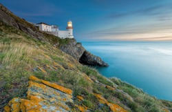As daylight begins yielding to twilight, The Wicklow Lighthouse at Wicklow, Ireland