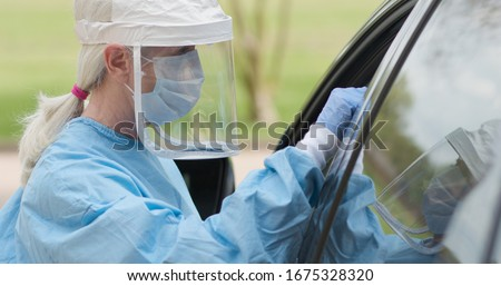 As part of the operations of a coronavirus mobile testing unit a healthcare worker dressed in full protective gear swabs an unseen person sitting inside of a vehicle.