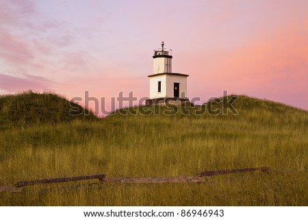 As the dawn sun comes up over the horizon, the lighthouse at Cattle Point on San Juan Island lights up as the sky behind glows with pink and magenta colors.
