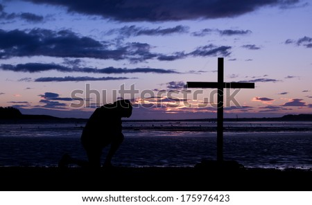 As the day ends a man kneels in pray before a cross.