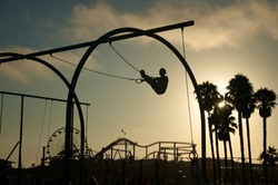 As the sun sets a silhouetted man works out on gymnast rings