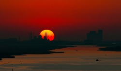 As the sun sets and illuminates the sky in red and in the foreground you see silhouette of the grand mosque with the sun in yellow orange on the horizon and a deep red purple sky