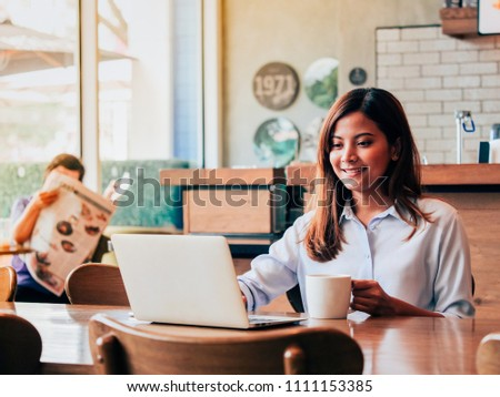 Asain woman working with laptop in coffee shop.