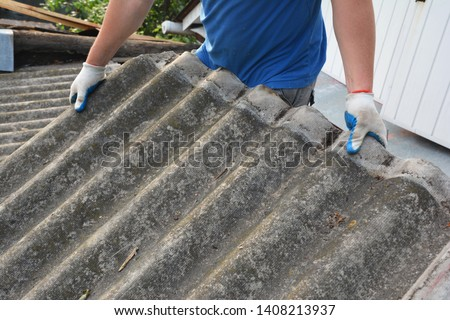 Asbestos removal roofer roof works. House with old, danger asbestos roof tiles repair and renovation.  Risks of Asbestos Roofs, Asbestos Roof Removal.