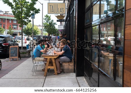 Asbury Park, NJ USA --June 18, 2017 -- Diners are seated at outdoor tables in Asbury Park on a summer day. Editorial Use Only