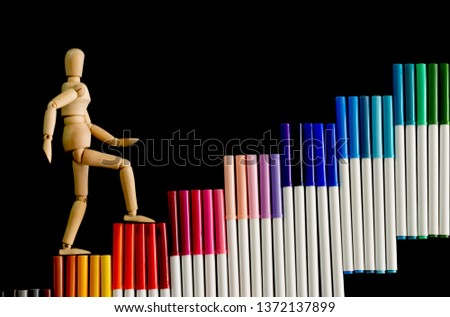 Ascending step stairs (by colorful marker pens)and wooden man model going upword isolated on dark background.Encourage motivation and inspiration to do something for success.Progression concept. #1372137899