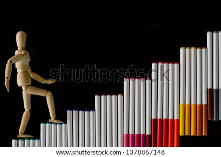 Ascending step stairs (by colorful marker pens)and wooden man model going upword isolated on dark background.Encourage motivation and inspiration to do something for success.Progression concept. #1378867148