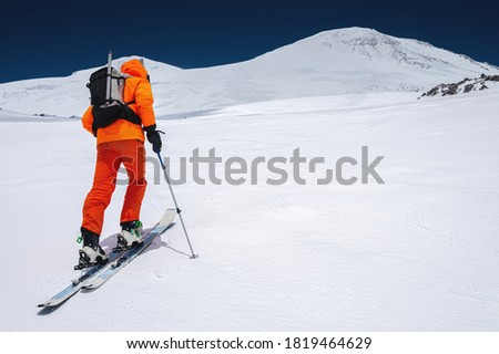 Ascent of a skier with a backpack in a mask and sunglasses on skis with poles to go uphill for freeride and backcountry. North Caucasus. Climbing Volcano Elbrus