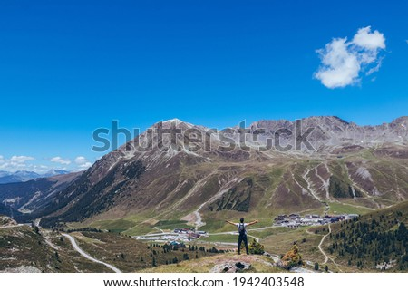 Ascent to the Finstertal dam at the Kuhtai ski resort in western Austria. The backpacker set out on an adventure. A man aged 20-24 of European descent of a lighter color stands on the edge of a rock. Foto stock ©
