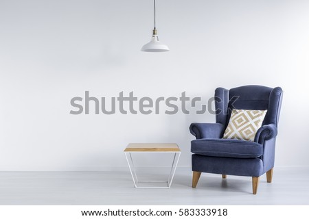 Ascetic room with blue armchair, side table and white lamp #583333918