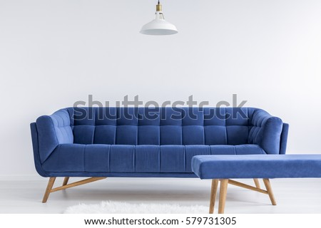 Ascetic white room with lamp, blue vintage sofa and bench #579731305