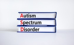 ASD, autism spectrum disorder symbol. Books with words 'ASD, autism spectrum disorder'. Beautiful white background. Medical and ASD, autism spectrum disorder concept. Copy space.