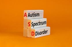 ASD, autism spectrum disorder symbol. Wooden blocks with words 'ASD, autism spectrum disorder'. Orange background. Medical and ASD, autism spectrum disorder concept. Copy space.