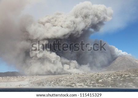 Ash cloud rising from pyroclastic flow from Soufriere Hills volcano approaching abandoned town of Plymouth, Montserrat