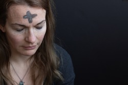 Ash cross on woman's forehead