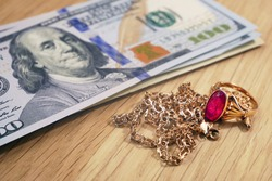 ash money and jewelry, pawn shop and buy and sell precious metals concept, golden rings, necklace bracelet o wooden background, closeup