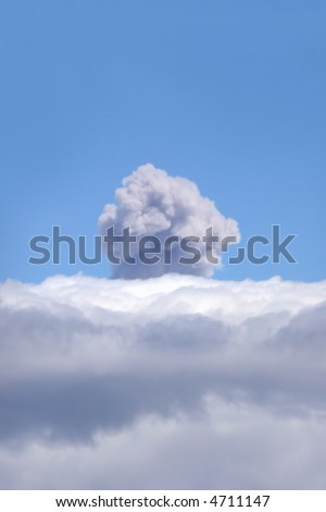 ash plume through clouds of an active volcano