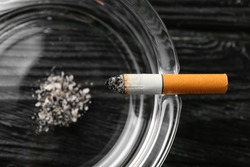 Ash tray and cigarette on dark wooden background, closeup
