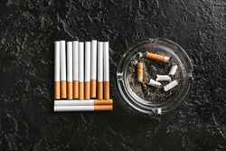Ash tray and cigarettes on dark background