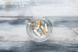 Ash tray with cigarettes on color wooden background