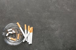 Ash tray with cigarettes on dark background