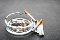 Ash tray with cigarettes on dark background, closeup