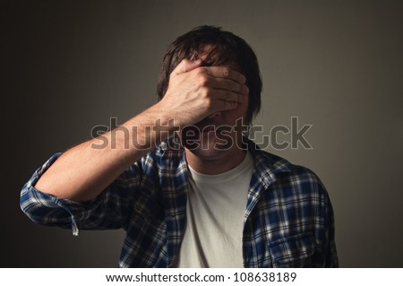 Ashamed man covering his eyes with hand, casual clothing, low light. Face palm, shame, problem, trouble, ignorance concept.
