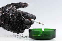 Ashed hand with a cigarette shows that smoking kills/Smoking kills