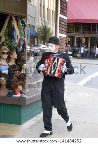 Asheville, North Carolina, USA - June 23, 2007: A mime street performer walks down the street playing an accordion in Downtown Asheville, North Carolina.