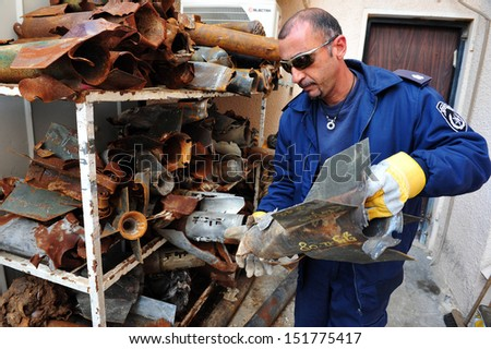 ASHKELON, ISR - JAN 02:Israeli Policeman from the bomb squad storing rockets fired from Gaza Strip on Jan 02 2009.Attacks began in 2001 and since then nearly 10,000 rockets have hit southern Israel.