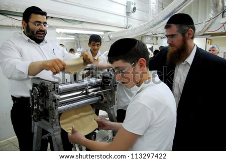 ASHKELON, ISRAEL - APRIL 14: Orthodox Jewish men prepare hand-made glat kosher matzah for Passover Jewish holiday on April 14 2008 in Ashkelon, Israel.