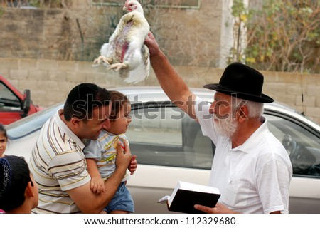 "ASHKELON - OCT 01 : Jewish man waves a chicken over his son and grandchild head during the ""Kaparot"" ceremony held on October 01 2006 in Ashkelon Israel."