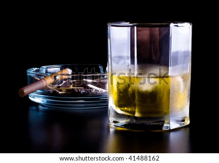 ashtray full of butts and glass of whiskey on black background