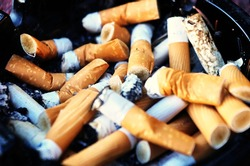 Ashtray full of cigarette butts close up. The cigarettes tobacco scraps can harm smokers  are toxic plastic pollution. Discarded cigarette butts and lung cancer concept.