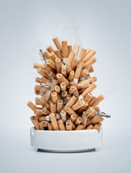 Ashtray full of cigarettes isolated on gray background with copy space