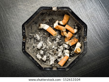 Ashtray on steel scratchy background