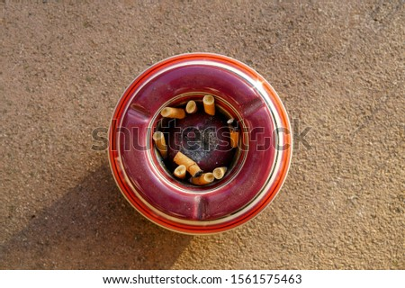ashtray with cigarettes. Modern cigarettes with a filter, with tobacco, a concept of smoking, bad habits. Crumpled bulls, broken cigarettes and tobacco in an ashtray. view from above