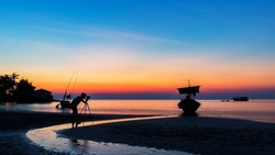Asia a man nature photographer,Photographer is taking a picture of sunrise at beach with beautiful sky reflections