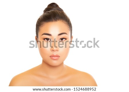 Asia Beauty. Beauty Portrait Brunette Asian Girl. Model looks directly at the camera, delicate smooth skin, beautiful light make-up, hair is gathered in a bun on the top over a white background.