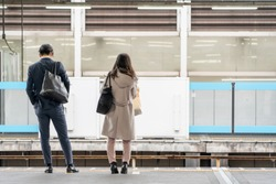 Asia Business concept for real estate and corporate construction - Asia business woman and man stand on train platform in background in Tokyo, Japan