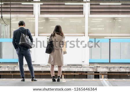 Asia Business concept for real estate and corporate construction - Asia business woman and man stand on train platform in background in Tokyo, Japan #1265646364