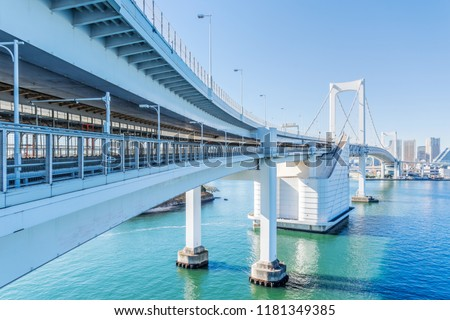 Asia Business concept for real estate and corporate construction - panoramic city skyline aerial view of tokyo bay, and rainbow bridge under blue sky in odaiba, Tokyo, Japan