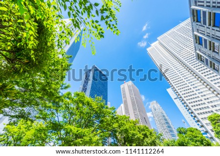 Asia Business concept for real estate, corporate construction and ecology - looking up view of panoramic modern city skyline with blue sky and green tree in shinjuku, tokyo, japan #1141112264